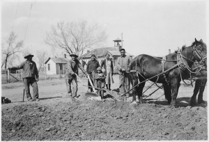 Tribal_Councilman_Henry_Ironshield_plows_garden_with_assistance_from_relatives_and_wife_-_NARA_-_285842
